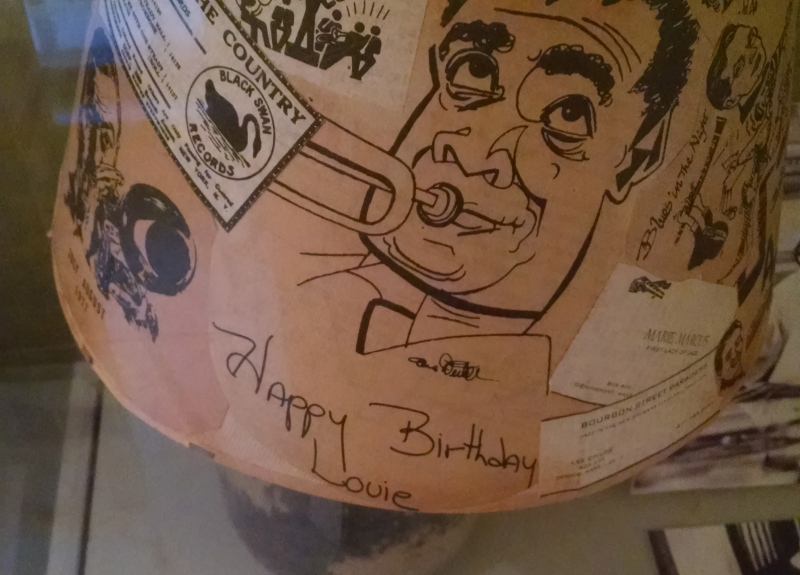 This lamp and lampshade was made by a fan of Louis Armstrong and gifted to him for his birthday. The glass base of the lamp is filled with rice and beans, Louis' favorite food. The shade is made from a collage of sketches, ticket stubs, and articles about Louis Armstrong.