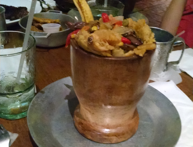 Mofongo is made of lightly fried green plantains, garlic, and other savory bits that are mashed together with a mortar and pestle — called a pilón — then filled with veggies and meats. Tostones are chip-like slices of fried plantains.