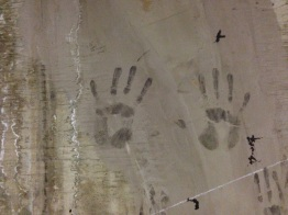 Hand prints on a wall.